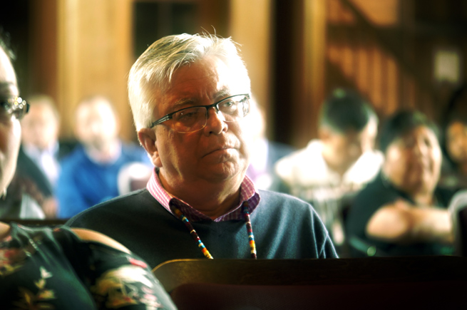 Man listening to a speaker at an Oweesta convening
