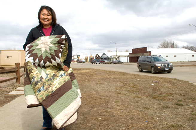 Native American woman holding a quilt in Eagle Butte, South Dakota